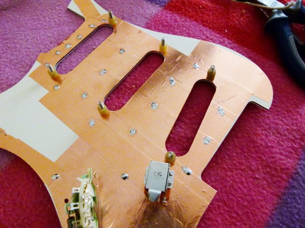 Installation des vis de réglages des micros sur le pickguard d'une Stratocaster